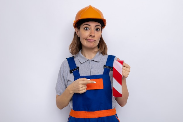 Young builder woman in construction uniform and safety helmet holding adhesive tape pointing with index finger at it  confused standing over white wall