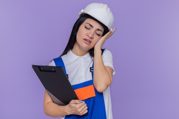 Giovane donna del costruttore in uniforme da costruzione e casco di sicurezza che tiene appunti che sembra stanco e sovraccarico di lavoro in piedi sopra la parete viola