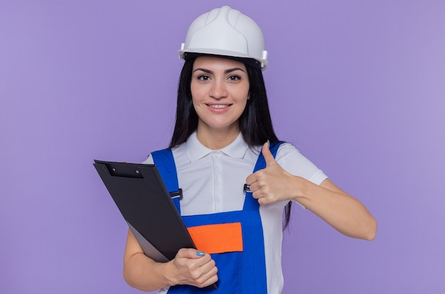 Giovane donna del costruttore in uniforme da costruzione e casco di sicurezza che tiene appunti