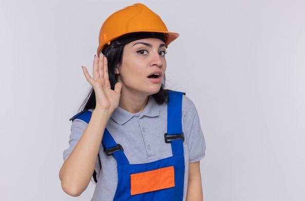 Young builder woman in construction uniform and safety helmet holding hand over her ear trying to listen to gossips standing over white wall
