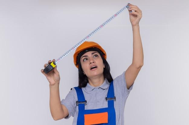 Giovane donna del costruttore in uniforme da costruzione e casco di sicurezza che tiene il nastro di misura guardandolo con la faccia seria che sta sopra il muro bianco