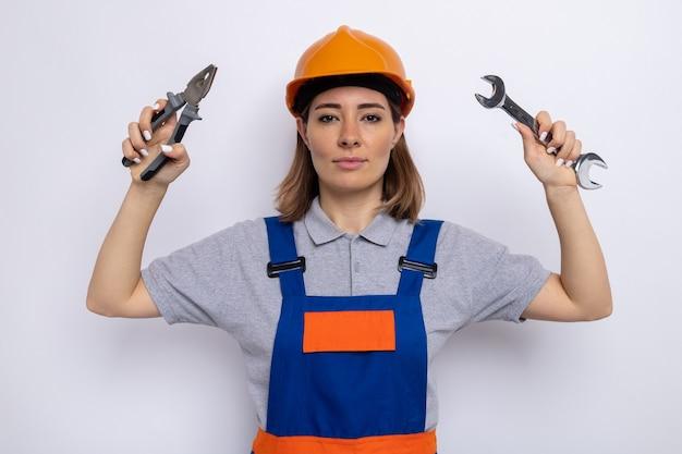 Giovane donna del costruttore in uniforme da costruzione e casco di sicurezza che tiene la chiave e le pinze con un'espressione seria e sicura in piedi sul muro bianco