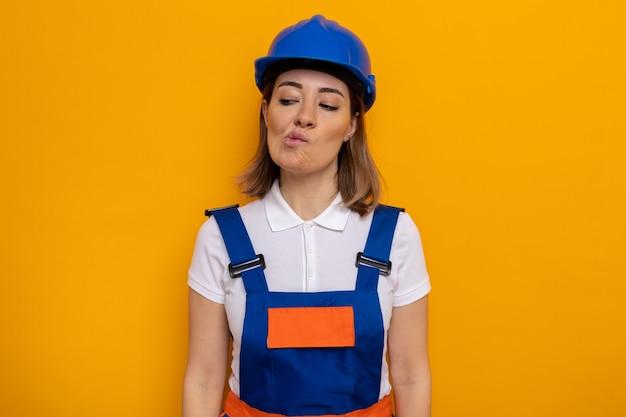 Giovane donna del costruttore in uniforme da costruzione e casco di sicurezza che guarda da parte confusa facendo bocca storta in piedi sul muro arancione