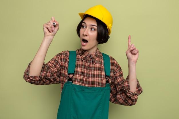 Giovane donna del costruttore in uniforme da costruzione e casco di sicurezza che guarda da parte felice e sorpresa che scrive in aria con la penna in piedi sul verde
