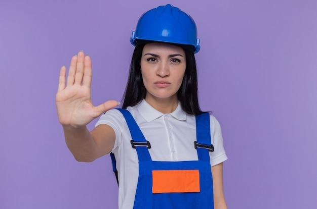 Giovane donna del costruttore in uniforme da costruzione e casco di sicurezza che guarda l'obbiettivo