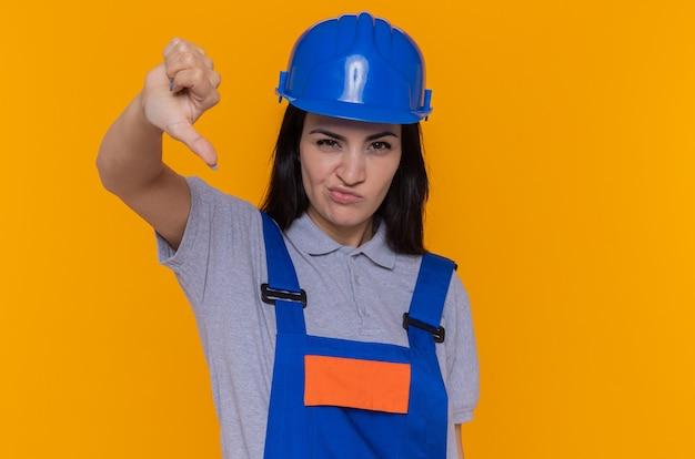 Giovane donna del costruttore in uniforme della costruzione e casco di sicurezza che esamina la parte anteriore dispiaciuta che mostra il pollice giù che si leva in piedi sopra la parete arancione