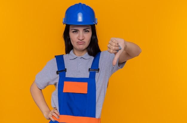 Giovane donna del costruttore in uniforme della costruzione e casco di sicurezza che esamina la parte anteriore dispiaciuta che mostra i pollici giù che si levano in piedi sopra la parete arancione