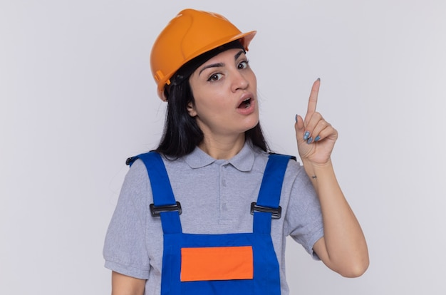 Giovane donna del costruttore in uniforme da costruzione e casco di sicurezza guardando davanti sorpreso mostrando il dito indice che ha una nuova buona idea in piedi sopra il muro bianco