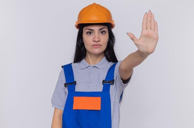 Giovane donna del costruttore in uniforme da costruzione e casco di sicurezza che guarda anteriore con faccia seria che fa gesto di arresto con la mano in piedi sul muro bianco
