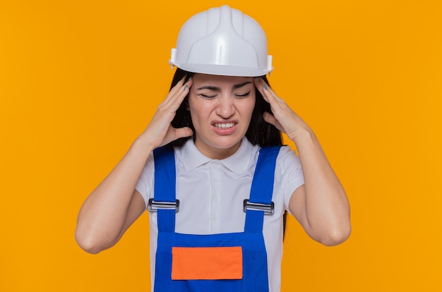 Young builder woman in construction uniform and safety helmet looking unwell touching her head with hands suffering from strong headache standing over orange wall