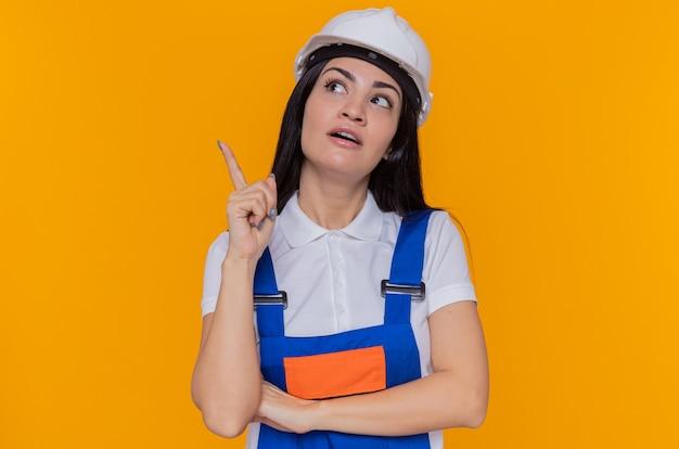 Giovane donna del costruttore in uniforme della costruzione e casco di sicurezza che osserva in su con il sorriso sul pensiero astuto del fronte che mostra il dito indice che ha grande idea che sta sopra la parete arancione