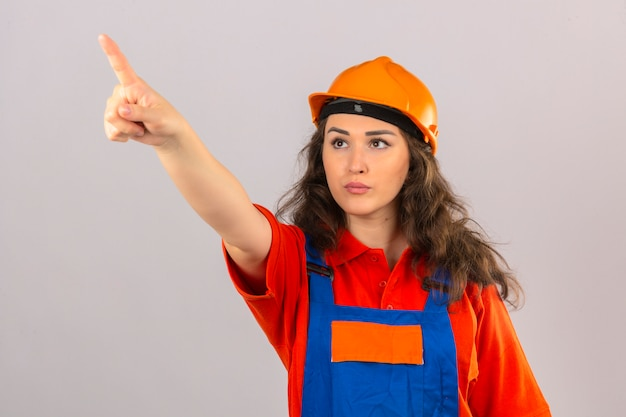 Young builder woman in construction uniform and safety helmet pointing to somewhere with finger looking seriously over isolated white wall