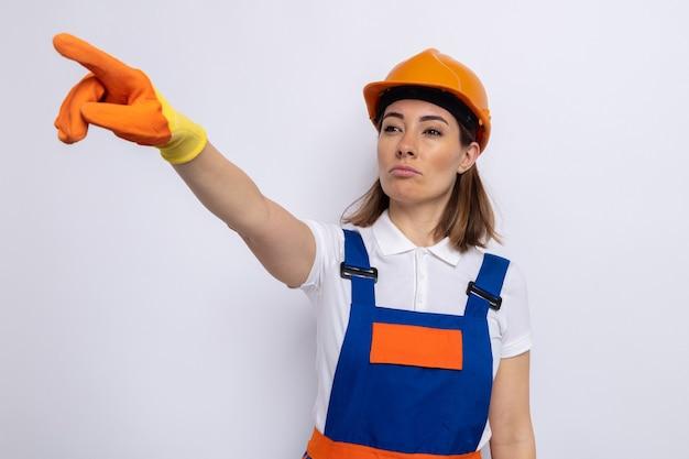 Giovane donna del costruttore in uniforme da costruzione e casco di sicurezza in guanti di gomma che guarda da parte con la faccia seria che punta con il dito indice a qualcosa in piedi su bianco