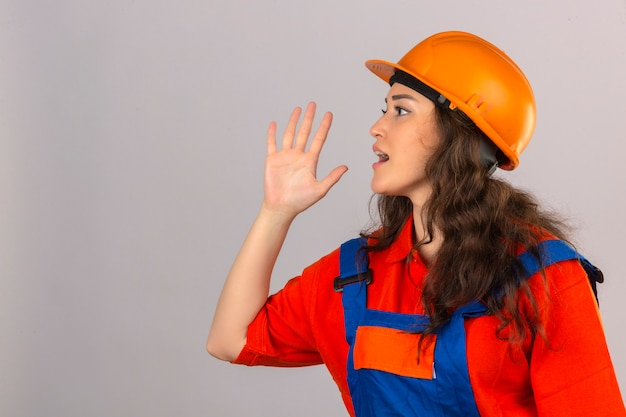 Young builder woman in construction uniform and safety helmet shouting to side with hand on mouth over isolated white wall