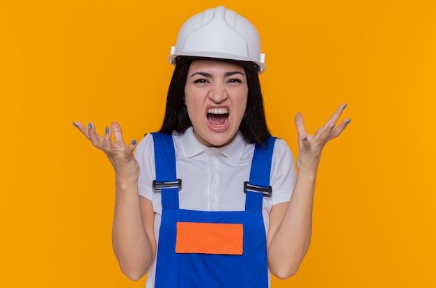 Giovane donna del costruttore in uniforme della costruzione e grida del casco di sicurezza