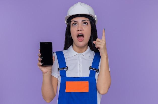 Giovane donna del costruttore in uniforme da costruzione e casco di sicurezza che mostra lo smartphone che osserva in su sorpreso che mostra il dito indice che ha grande idea che sta sopra la parete viola