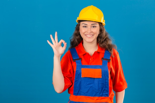 Young builder woman in construction uniform and safety helmet smiling cheerfully doing ok sign over isolated blue wall
