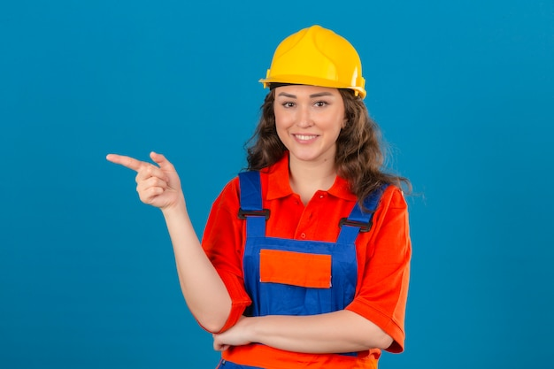 Young builder woman in construction uniform and safety helmet smiling cheerfully looking confident pointing with index finger to the side over isolated blue wall