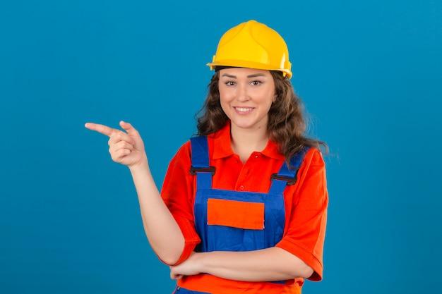 Giovane donna del costruttore in uniforme della costruzione e casco di sicurezza che sorridono allegramente sembrando indicare sicuro con il dito indice al lato sopra la parete blu isolata
