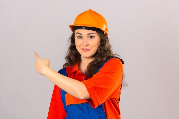 Giovane donna del costruttore nell'uniforme della costruzione e nell'indicare sorridente del casco di sicurezza con la mano ed il dito il lato sopra la parete bianca isolata