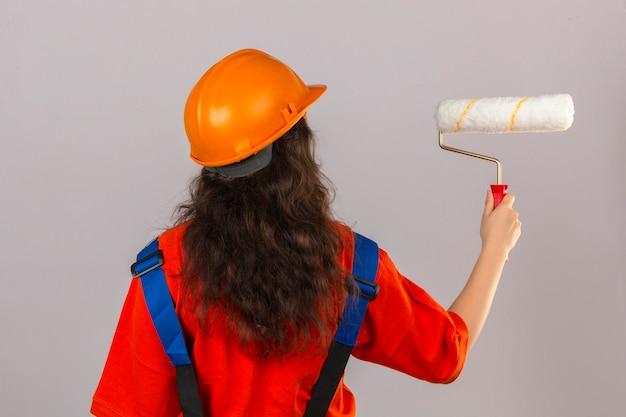 Giovane donna del costruttore in uniforme della costruzione e casco di sicurezza che stanno indietro con il rullo di pittura sopra la parete bianca isolata