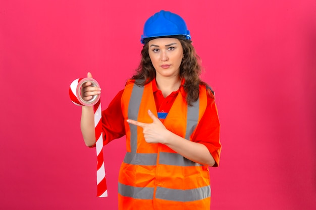 Young builder woman in construction uniform and safety helmet standing with adhesive tape and pointing at it with index finger frowning over isolated pink wall