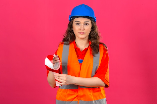 Young builder woman in construction uniform and safety helmet standing with adhesive tape with serious face over isolated pink wall_