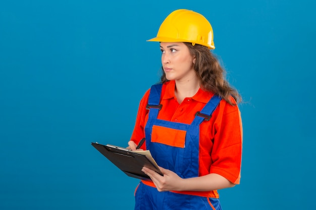 Young builder woman in construction uniform and safety helmet standing with clipboard making notes in it over isolated blue wall