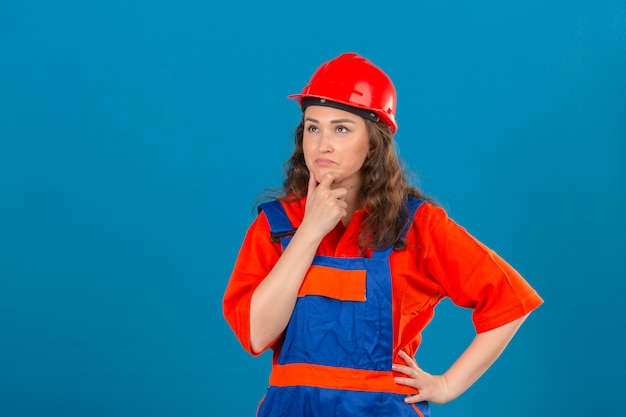 Young builder woman in construction uniform and safety helmet standing with hand on chin thinking having doubts over isolated blue wall