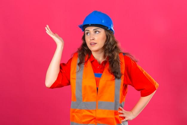 La giovane donna del costruttore in uniforme della costruzione e casco di sicurezza che stanno con la mano sollevata gesturing deludente non hanno concetto di idea sopra la parete rosa isolata