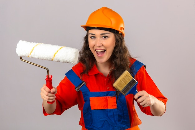 Young builder woman in construction uniform and safety helmet standing with paint roller and brush smiling cheerfully over isolated white wall