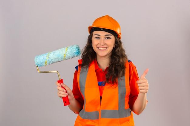 Giovane donna del costruttore in uniforme della costruzione e casco di sicurezza che stanno con il rullo di pittura che sorride allegramente sopra la parete bianca isolata