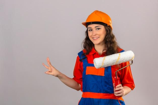 Giovane donna del costruttore in uniforme della costruzione e casco di sicurezza che stanno con il rullo di pittura che sorride allegramente e che mostra facendo segno tre con le dita sopra la parete bianca isolata