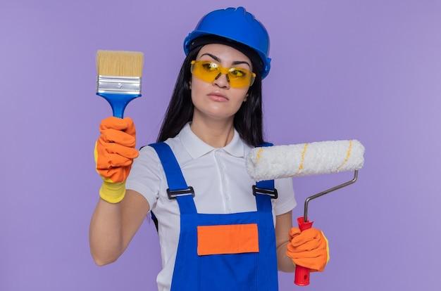 Giovane donna del costruttore in uniforme da costruzione e casco di sicurezza che indossa guanti di gomma che tengono il rullo di vernice e la spazzola guardandolo con la faccia seria che sta sopra la parete viola