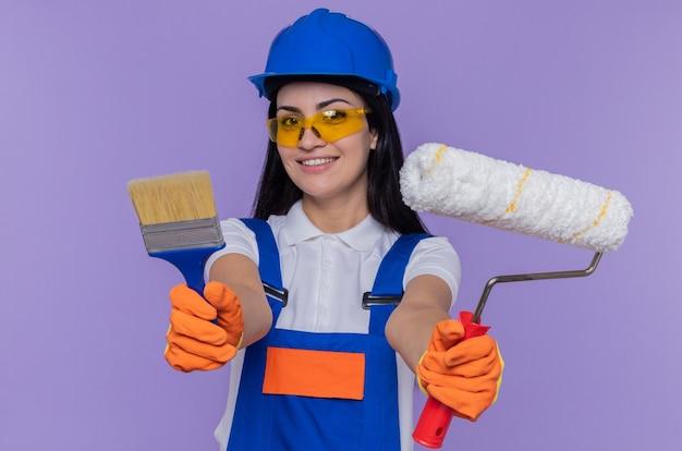 Giovane donna costruttore in uniforme da costruzione e casco di sicurezza che indossa guanti di gomma che tengono rullo di vernice e pennello