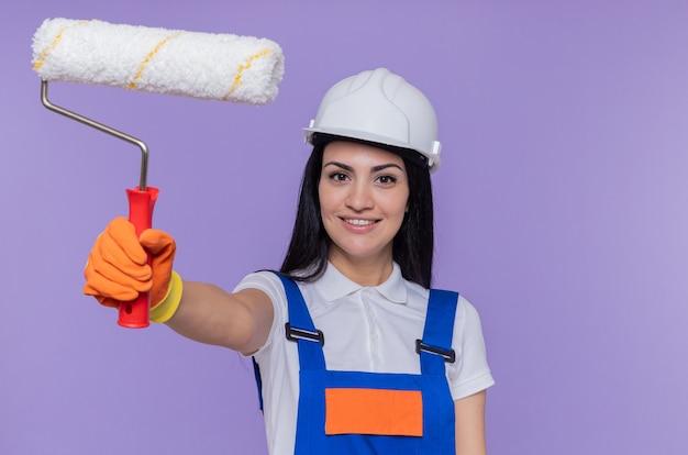 Giovane donna costruttore in uniforme da costruzione e casco di sicurezza che indossa guanti di gomma tenendo il rullo di vernice