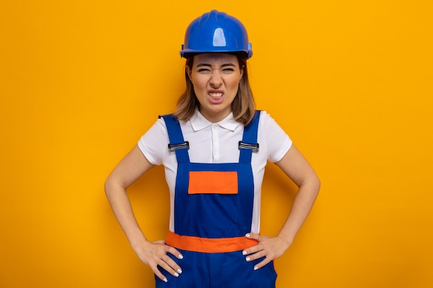 Young builder woman in construction uniform and safety helmet with angry face with arms at hip standing on orange