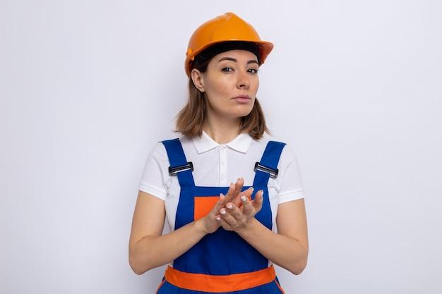 Giovane donna del costruttore in uniforme da costruzione e casco di sicurezza con un'espressione seria e sicura che applaude in piedi sul muro bianco