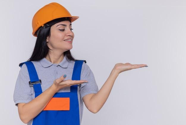 Giovane donna del costruttore in uniforme da costruzione e casco di sicurezza