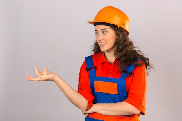 Молодая женщина строитель в строительной форме и защитный шлем, задавая вопросы с поднятой рукой, стоя над изолированной белой стене