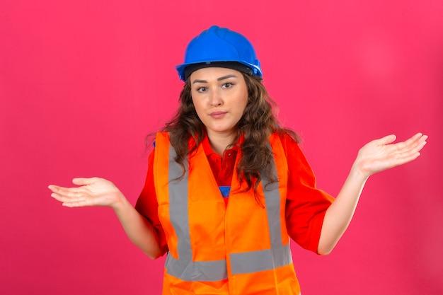建設の制服と安全ヘルメットの若いビルダー女性無知と腕と手で混乱した表現は孤立したピンクの壁に疑問の概念を発生