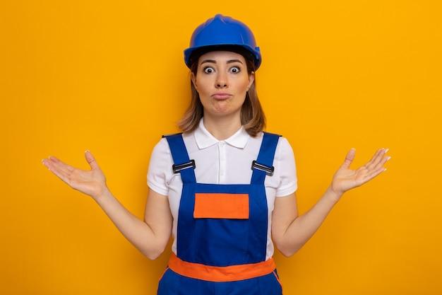 건설 유니폼과 안전 헬멧을 쓴 젊은 건축업자 여성은 주황색 위에 서서 대답이 없는 팔을 양쪽으로 벌리고 혼란스러워했다
