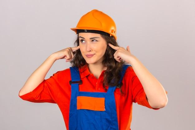 격리 된 흰 벽에 소음에 대 한 짜증 식 손가락으로 귀를 덮고 건설 유니폼과 안전 헬멧에 젊은 작성기 여자