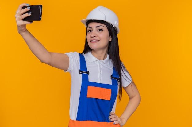 Молодая женщина-строитель в строительной форме и защитном шлеме делает селфи с помощью смартфона, уверенно улыбаясь, стоя над оранжевой стеной