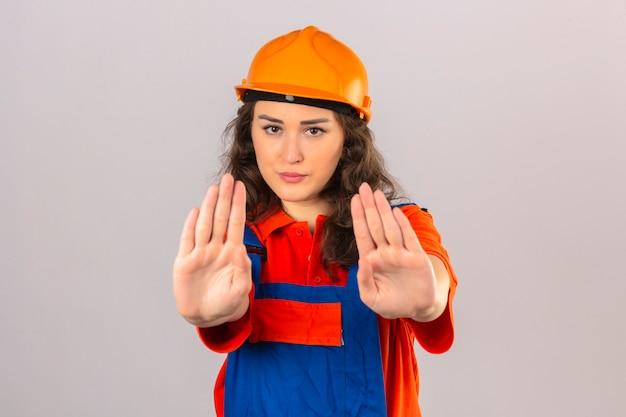 Молодая женщина строитель в строительной форме и защитный шлем делает остановки петь ладонями руки, предупреждающие выражение над изолированной белой стеной