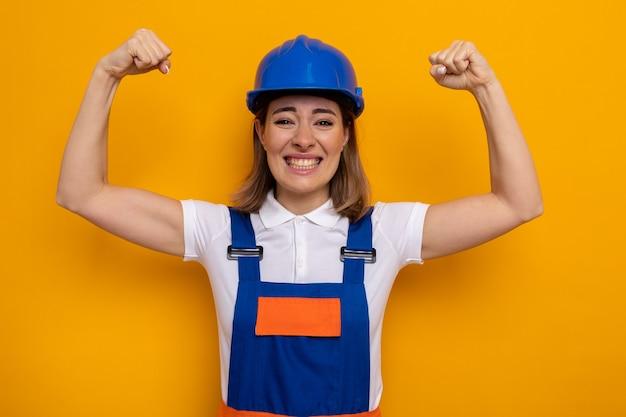 オレンジ色の壁の上に立っている勝者のように幸せで興奮したくいしばられた握りこぶしを上げる建設制服と安全ヘルメットの若いビルダーの女性