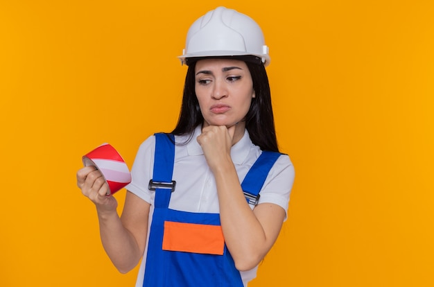 オレンジ色の壁の上に立って考えているあごに手でそれを見て粘着テープを保持している建設制服と安全ヘルメットの若いビルダーの女性