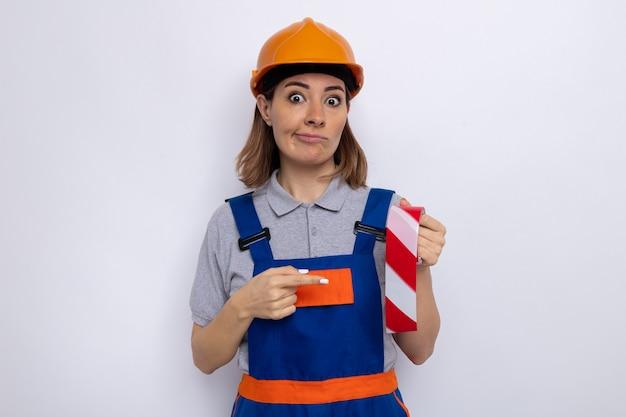 건설 유니폼을 입은 젊은 건축업자 여성과 검지 손가락으로 가리키는 접착 테이프를 들고 있는 안전 헬멧은 흰 벽 위에 서 있는 것을 혼란스럽게 생각합니다