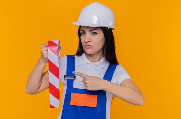 オレンジ色の壁の上に立っている深刻な顔で人差し指でそれを指している粘着テープを保持している建設制服と安全ヘルメットの若いビルダー女性