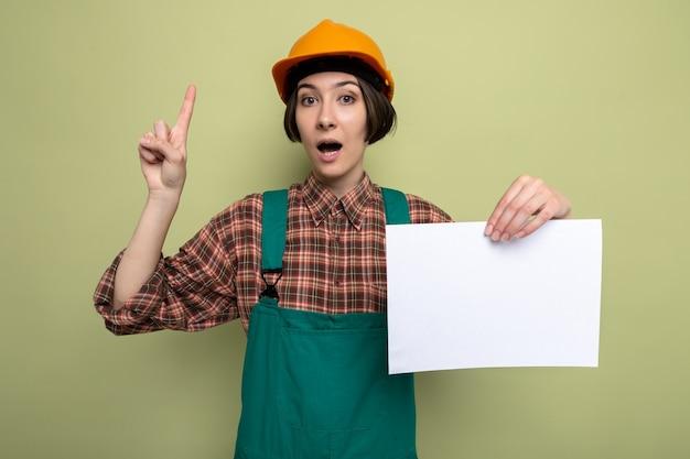 Молодая женщина-строитель в строительной форме и защитном шлеме, держащая пустую страницу, удивлена, показывая указательный палец, стоящий на зеленом